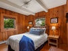 Knotty pine paneling makes this master bedroom a cozy place to fall asleep to the sound of the waves