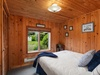 This bedroom has a cozy cabin feel with lots of natural light